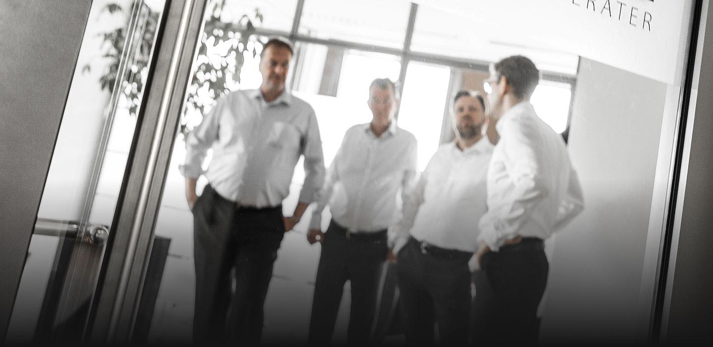 Die Partner in einer Teambesprechung (stehend): Herr Reinhardt, Herr Bochenek, Herr Heuer, Herr Hoffmeister